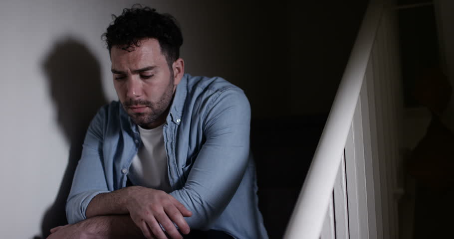 4K Depressed man sitting alone on the stairs at home. Loneliness concept, could be struggling with addiction or mental health issues or a victim of domestic abuse