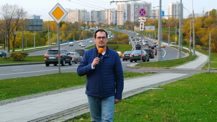 Middle-aged man tv correspondent leads a report with a microphone against the background of the city traffic | Shutterstock HD Video #32318476