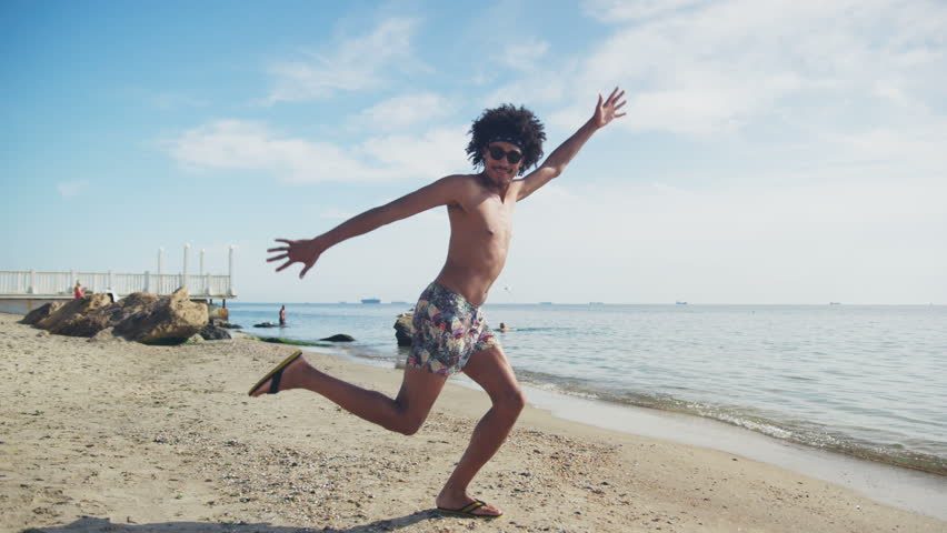 Young man dances on the beach funny good-looking handsome healthy hot men beautiful ifestyle male sea sky summer american Slow Motion Shot on RED Epic Camera.