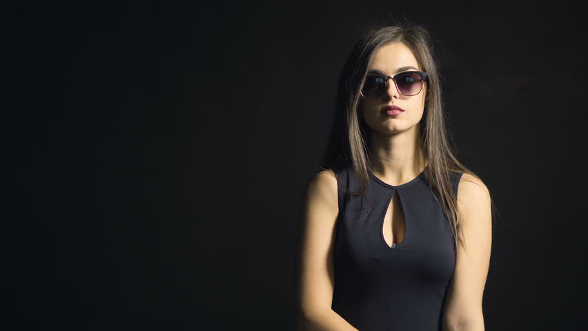 Portrait of beautiful caucasian girl, in cool sunglasses and sexy black dress, on black friday in the black background