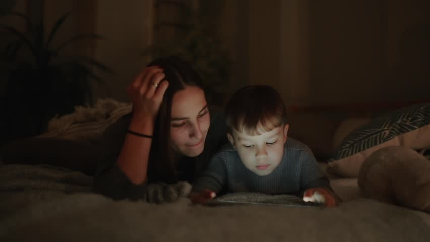 Happy family mother and son lying on the bed in the bedroom of his house playing games the screen of the tablet #32329723