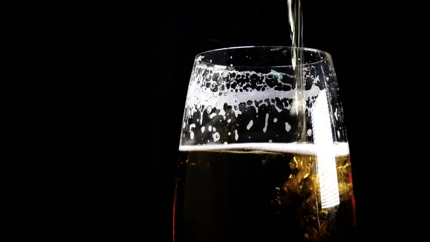 A lager beer is poured into a glass in close up