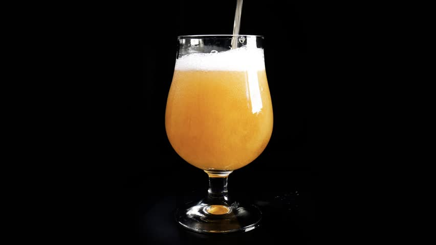 Pouring light beer into glass against black background