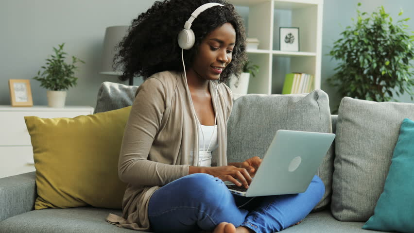 Young curly African American woman in the white headphones taping on her laptop while sitting on the couch in the living room. | Shutterstock HD Video #32334328