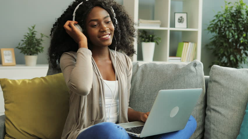 Pretty young curly African American woman in the white headphones listening to the music, dancing and working on her laptop while sitting on the sofa. Indoor. | Shutterstock HD Video #32334337