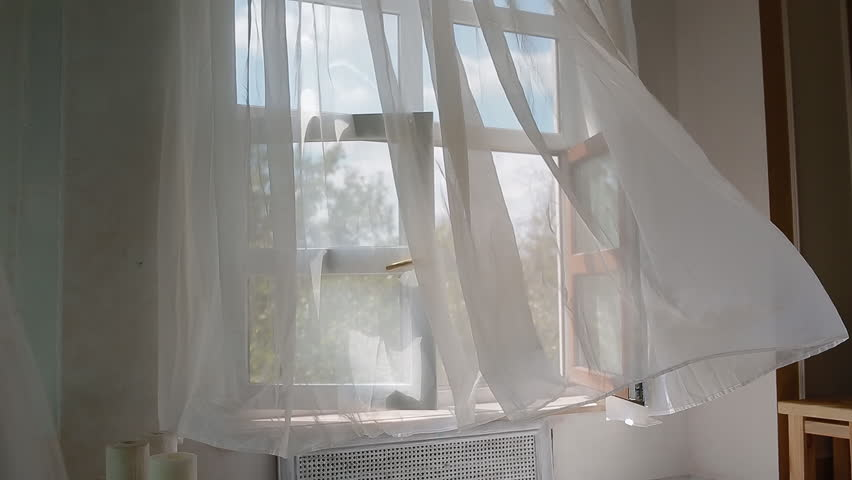 Open window with white curtain moving on the wind. Tranquil background.