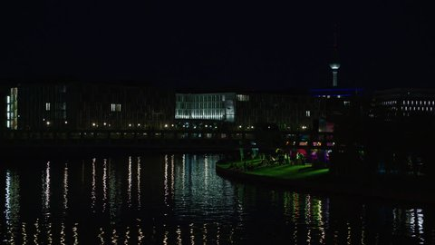 May, 2017 Berlin, Germany. Night skyline of the government buildings with TV Tower and Spree river with light reflections next to a riverside bar in super wide.