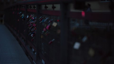 May, 2017 Berlin, Germany. Rack focus of locks latched onto a bridge at dusk with traffic in the background.