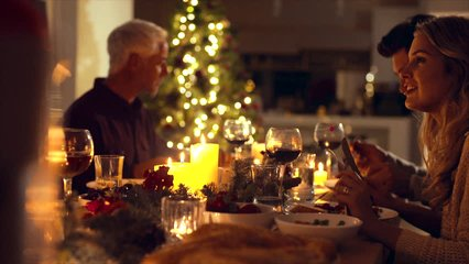 Christmas eve dinner, family sitting at dining table enjoying dinner together. Family celebrating christmas together at home.