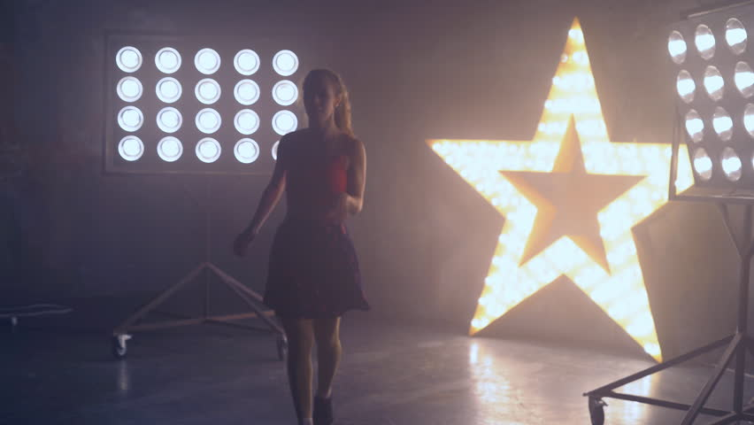 A young professional dancer performs a fast number on stage in the light of the spotlights. a woman in a short skirt and a tall top. A girl is dancing on stage using a smoke machine. Spotlights in the | Shutterstock HD Video #32353042