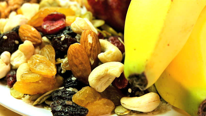 Selection of fresh & dried fruits, nuts & cereal bars to eat as healthy snack food options