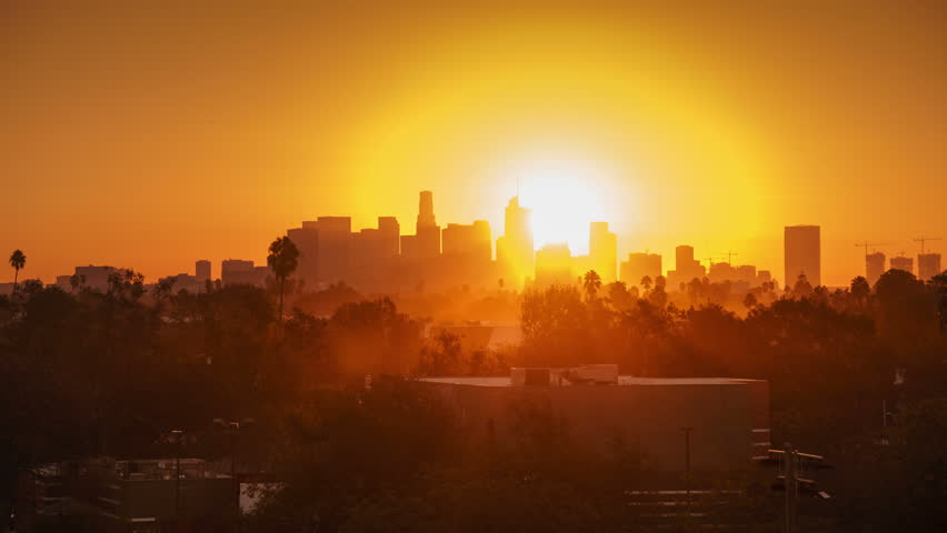Sunrise over city, closeup on modern downtown Los Angeles skyline buildings silhouettes. 4K UHD timelapse.