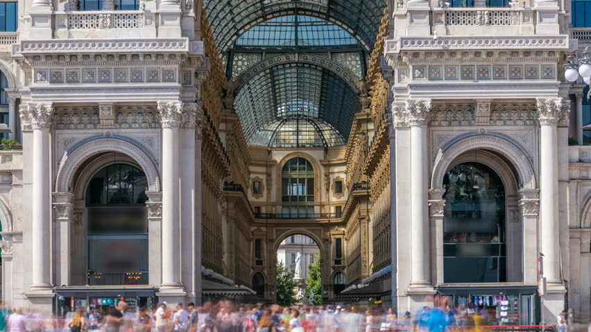 Entrance to the Galleria Vittorio Emanuele II timelapse on the Piazza del Duomo (Cathedral Square). This gallery is tourist attraction of Milan. Blue cloudy sky at summer day. People walking inside