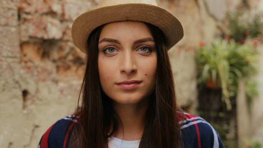 Portrait of brown-haired young charming woman with gray blue eyes. Woman looking at camera and smiling. Outdoor. Close-up | Shutterstock HD Video #32369701