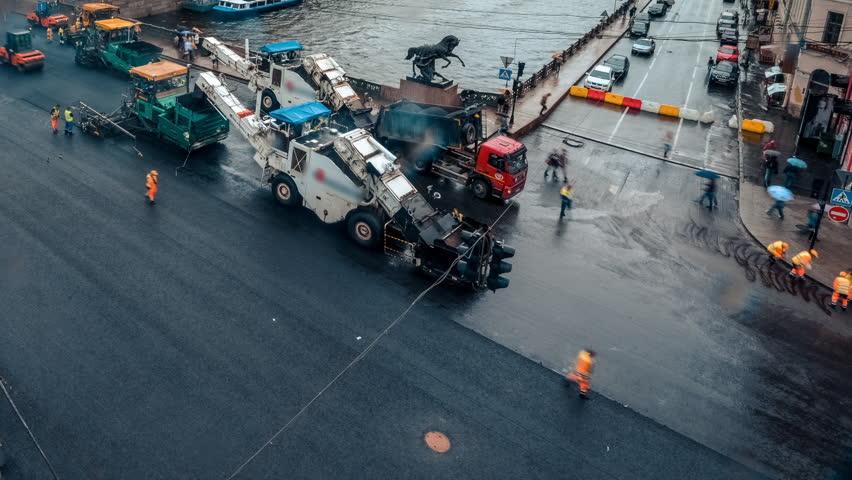 Saint Petersburg, repair of roads, Nevsky Prospect, asphalt paver, people in the vests, time laps
