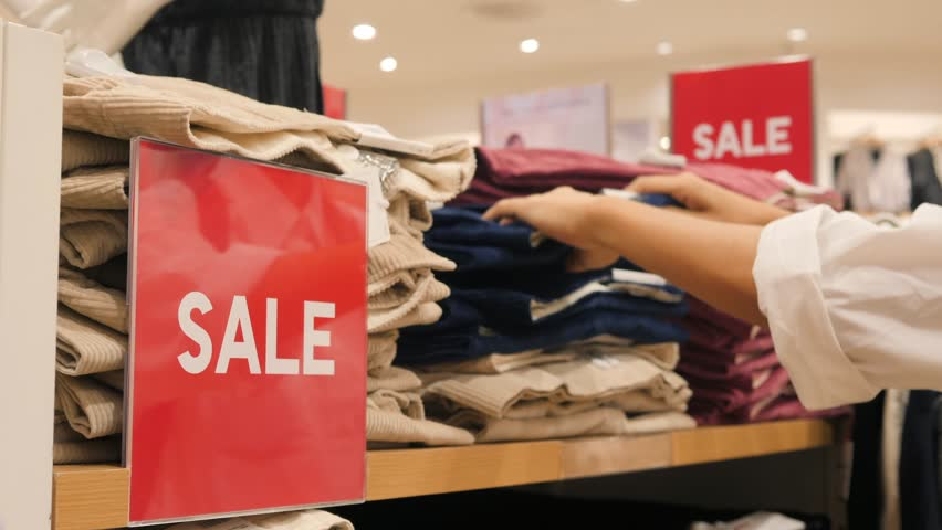Female Hands Choosing Jeans from Stack in Clothing Store. Big Red Sale Sign in Shopping Mall. Black Friday Concept. 4K. | Shutterstock HD Video #32375464
