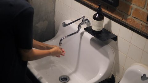 Woman Washing Her Hands in Sink in Loft Style Bathroom with Brick Walls. 4K, Hygiene Concept.