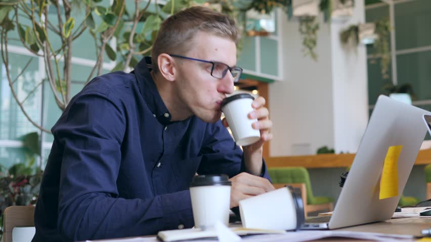 Funny Crazy Businessman with Caffeine Addiction Drinking Coffee and Typing on Laptop Very Fast in the Office. 4K. | Shutterstock HD Video #32375710