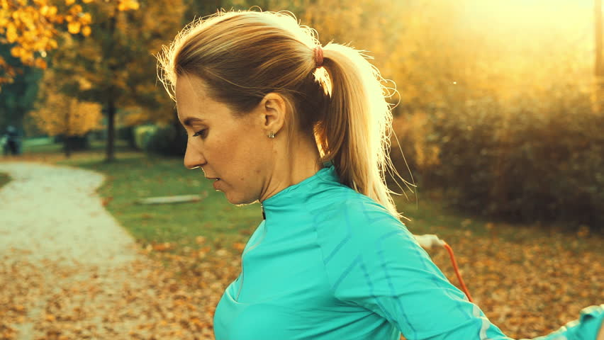 Fitness woman jumping rope. Female is jogging in sunny day light in the autumn trees background, girl training outdoors on fall day   Shutterstock HD Video #32379769