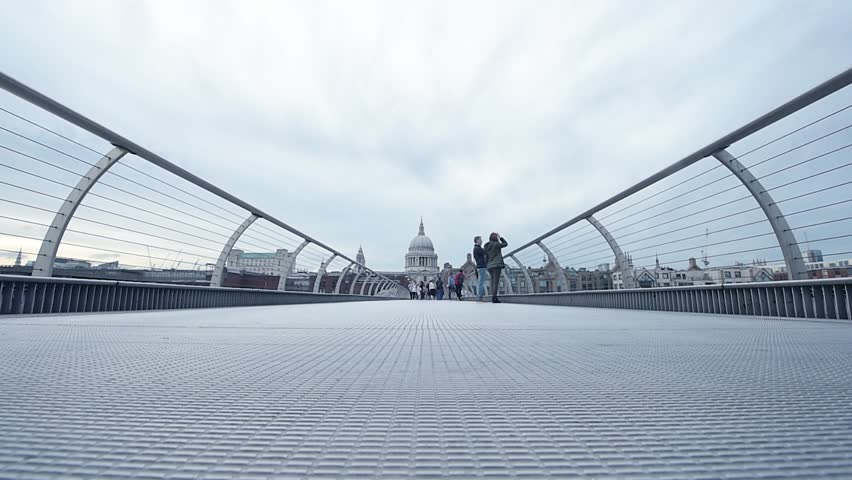 London, United Kingdom - Circa 2017: Young couple and other people tourists walking on Millennium Bridge with majestic St Paul Cathedral behind at dusk #32382634