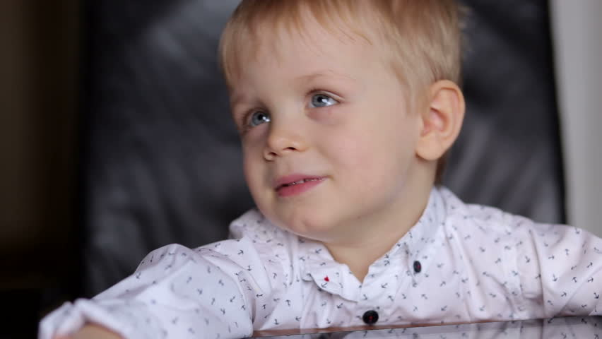 Portrait of little boy in a white shirt with tablet at the table. | Shutterstock HD Video #32396713