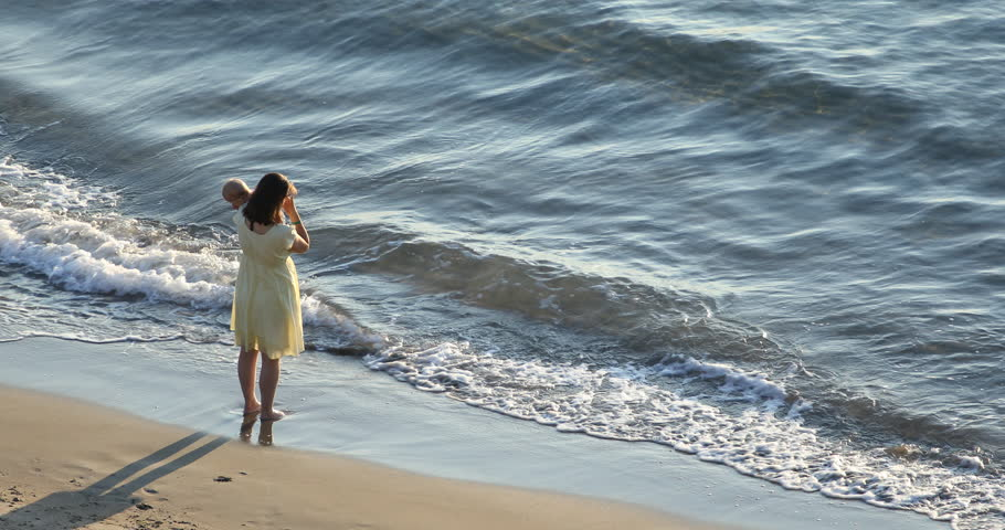 Mother standing on beach and holding baby in her arms, aerial view   Shutterstock HD Video #32409808
