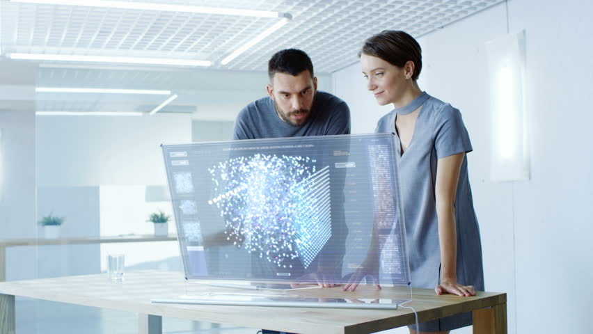 In the Near Future Male and Female Computer Engineers Talk While Working on the Transparent Display Computer. Screen Shows Interactive Neural Network, Artificial Intelligence Project. 4K UHD.