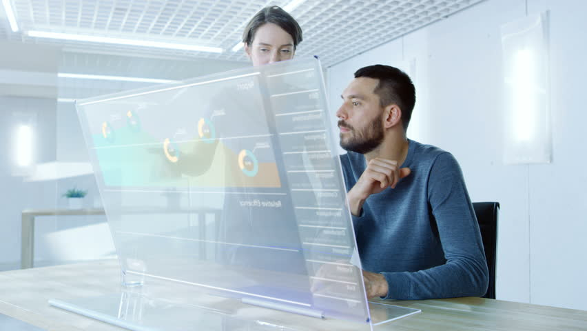 In the Near Future Male and Female Office Workers Discuss Graphical Statistic Shown on Transparent Computer Display. Beautiful People Talking. Interactive Charts on the Screen.