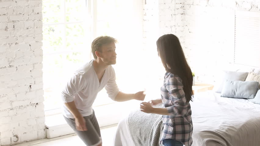 Young casual loving couple dancing in light cozy bedroom, performing twist or rock n roll dance elements, learning new moves, rehearsing funny dance at home, spinning turning around, hugging, laughing
