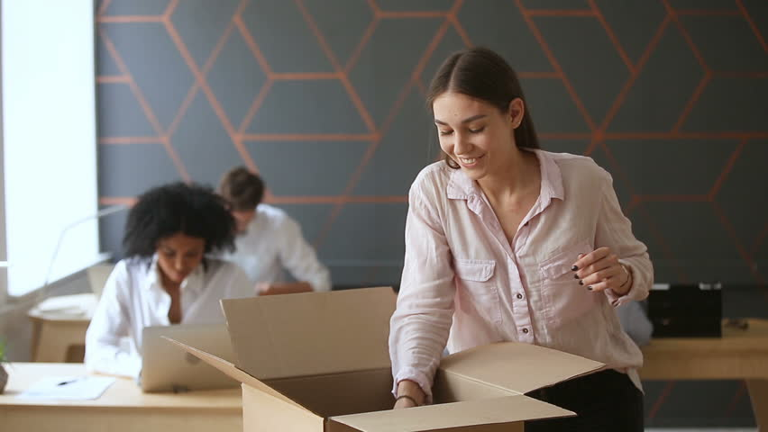 First day at new job concept, young happy woman unpacking box with her belongings standing near office desk, just hired smiling intern starting work in big company, moving into coworking space Royalty-Free Stock Footage #32413204