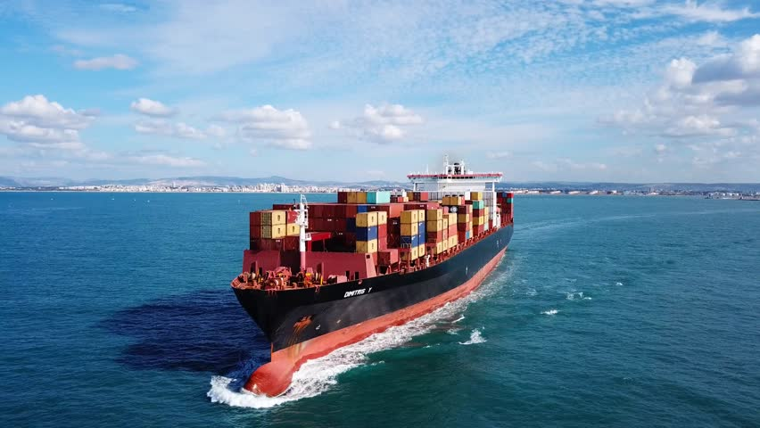 Mediterranean sea - October 25, 2017: Low angle view of a Large container ship at sea, loaded with various container brands - Aerial footage