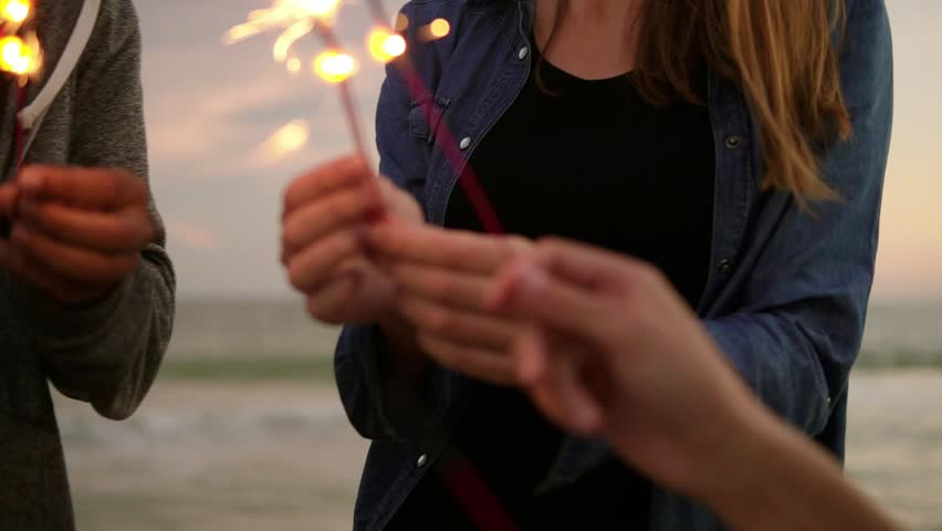 Closeup view of young people holding bengal lights during evening standing by the sea during sunset. Slowmotion shot