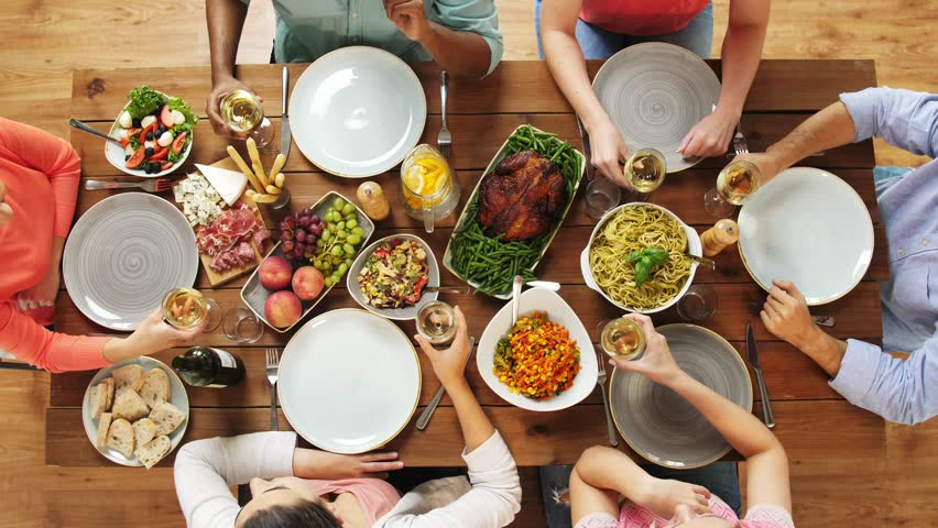eating and holidays concept - group of people at table with food clinking wine glasses #32420275