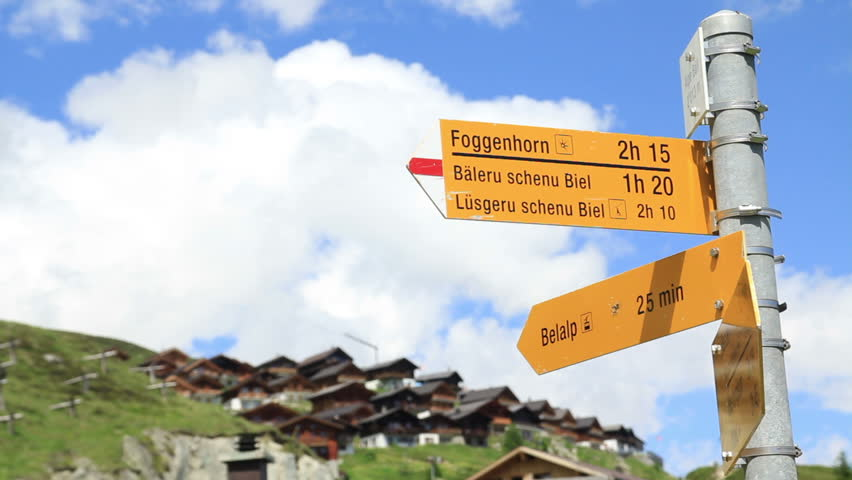 Yellow signboard for hikers in Belalp, Switzerland.