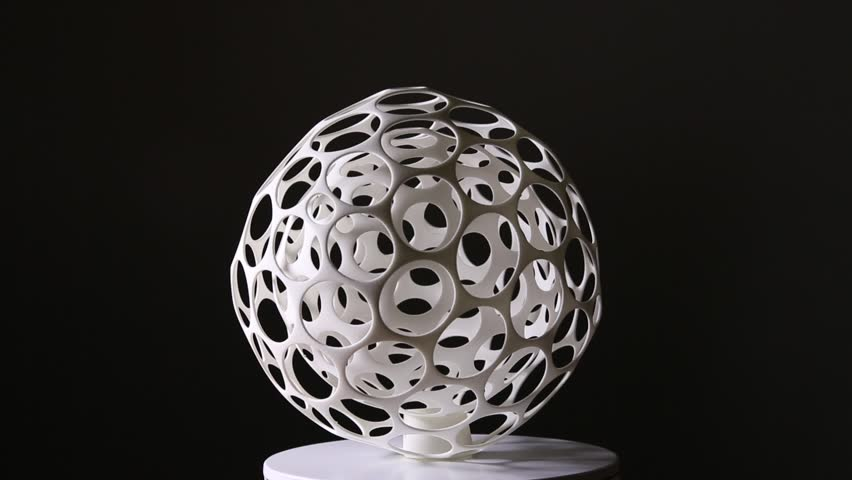 White spherical figure printed in 3D on a black background. The figure is spinning. Through 3D printing technology, these sculptures can be made in wireframe and hollow.