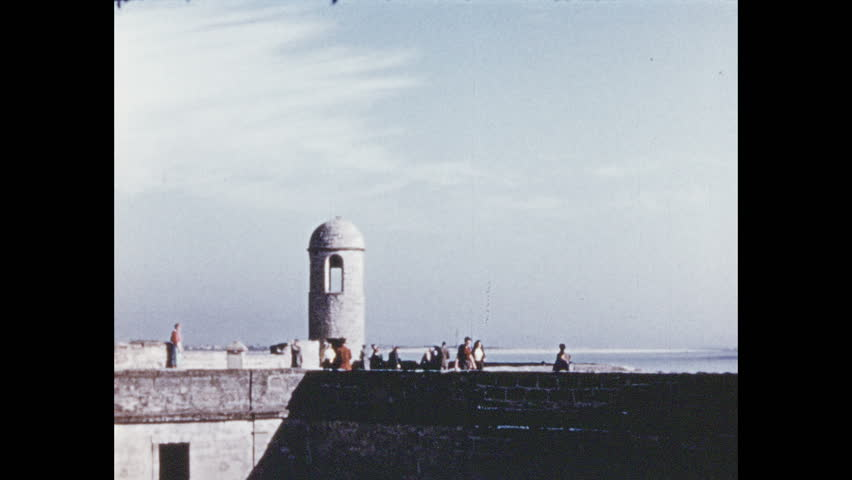 1950s: People walk around fort. Boy stares down while sitting at fort. Flock of birds fly in the sky.