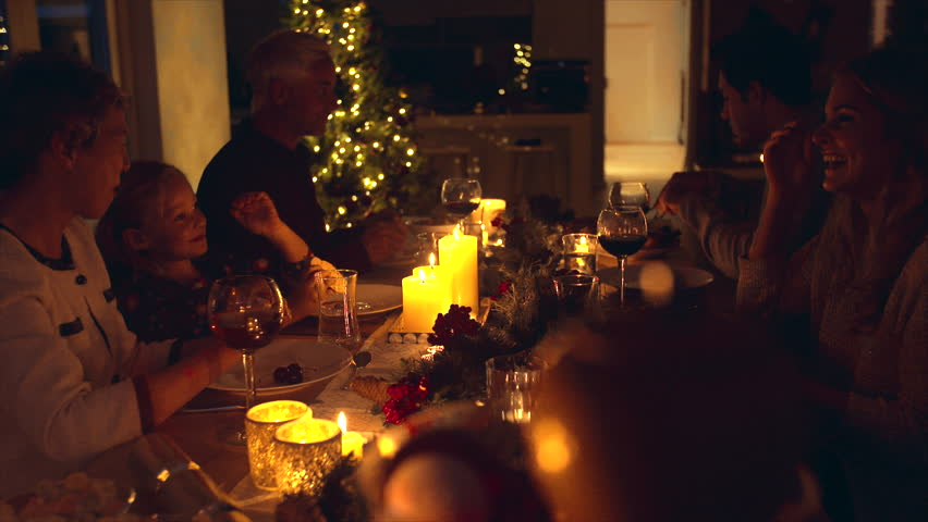 Extended family celebrating christmas together at home. Family of five sitting at dining table talking and having dinner together on Christmas eve. | Shutterstock HD Video #32437915