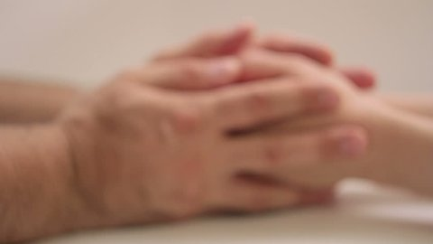 A man and a woman hold hands by gently touching and stroking. Close-up, out of focus