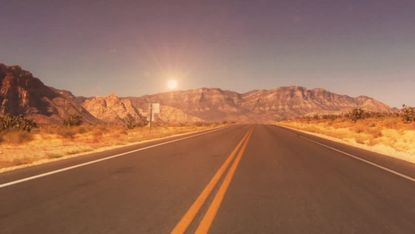 Desert road with sun and mountains