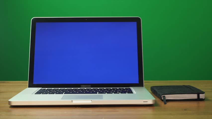 Laptop with a green screen and black notepad on table. Green screen background. Dolly shot. Zoom out motion | Shutterstock HD Video #32450818