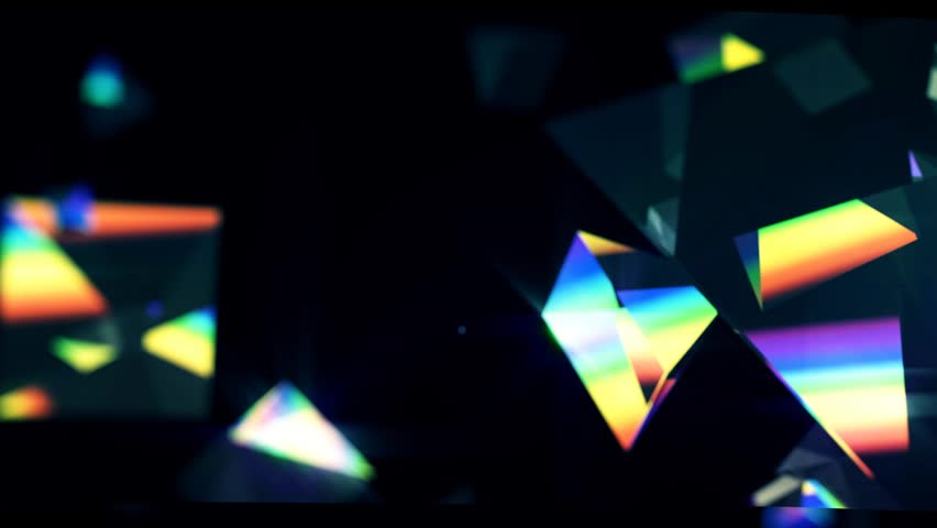 Rainbow triangle prisms float close up on black background