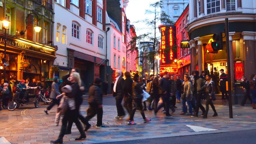 LONDON, ENGLAND, UNITED KINGDOM - APRIL, 2017:Night life of London Soho.People crossing illuminated Great Windmill street,Windmill International strip club,rickshaw pedicab riders waiting  passengers