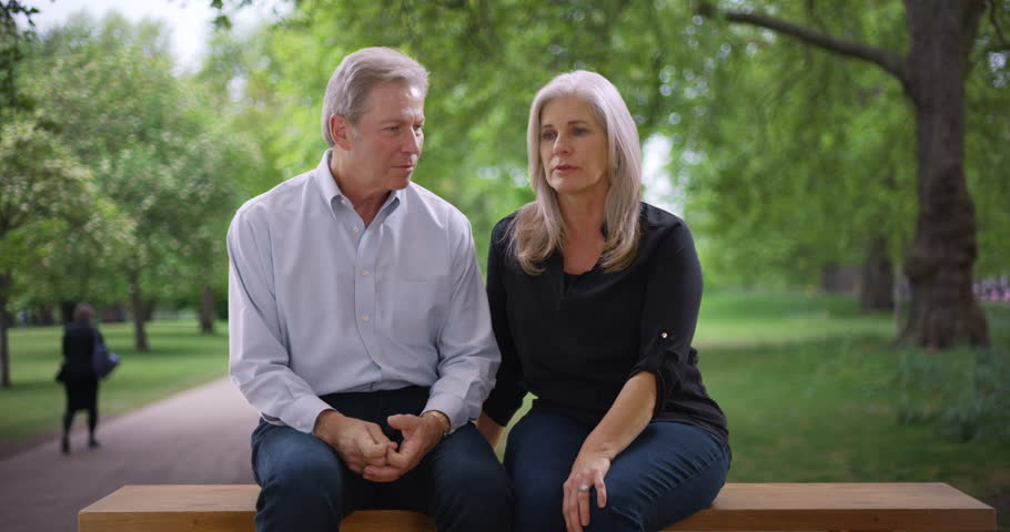 Aged white couple on a public park bench discuss a serious matter with each other. Older Caucasian woman and man at a park talk about something that happened recently. 4k | Shutterstock HD Video #32500603