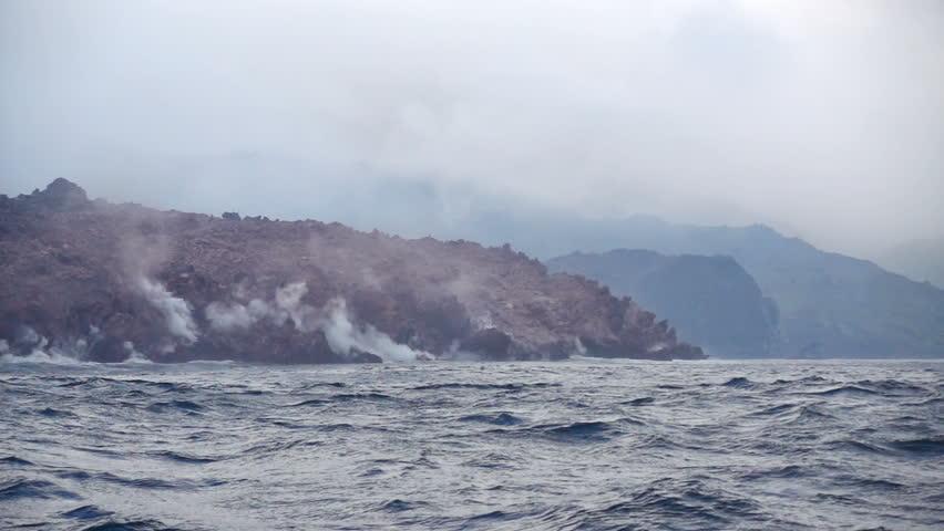 Okhotsk Sea, Chirpoy Island, Snow volcano activity, Russia. Hot volcanic lava falls into the sea. White fog rises over the shore.