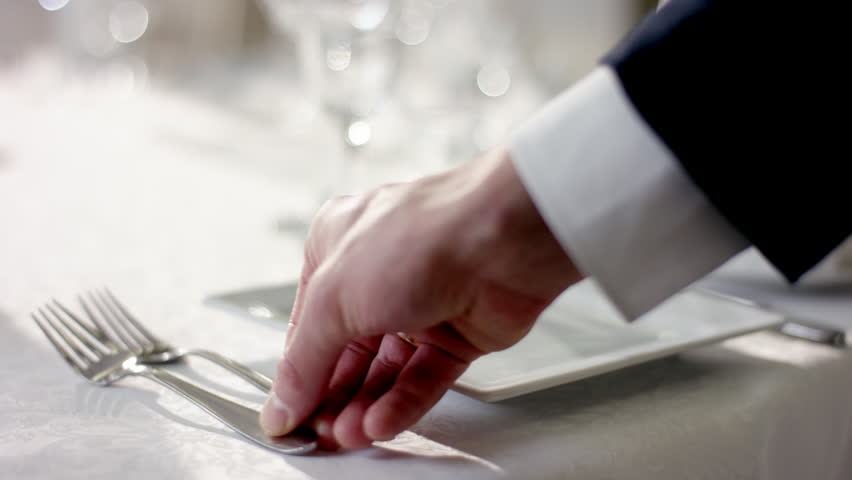 Shot of waiter hand correcting cultery on table before celebration at banquet hall
