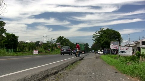 SAN JOSE, COSTA RICA - CIRCA JUNE 2012: Vehicles and pedestrians on rural road,  San Jose, Costa Rica , circa June 2012.
