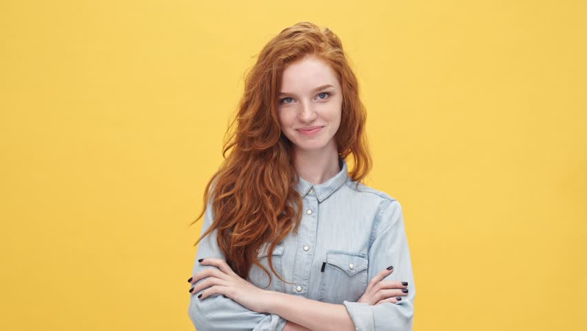 Smiling mystery ginger woman in denim shirt holding crossed arms and looking at the camera over yellow background