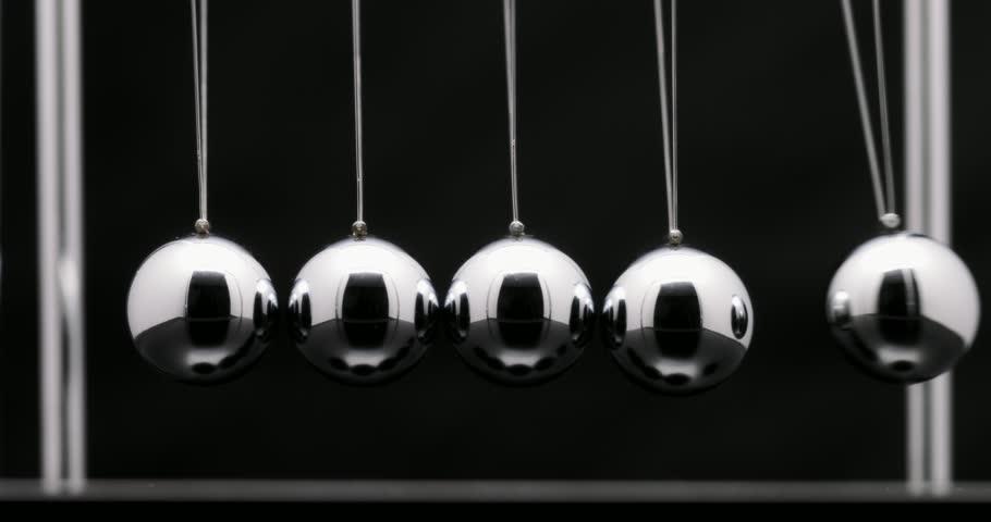 Newton's cradle office toy. Studio shot of swinging metal balls in slow motion on black background