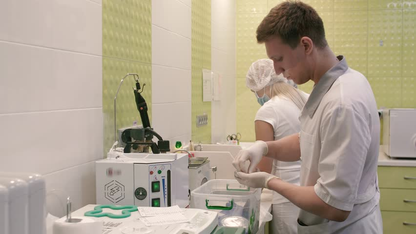 Close-up of a member of the medical laboratory. A young man prepares equipment for upcoming procedures. #32542153
