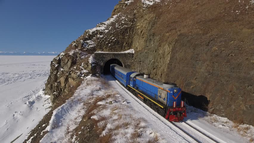 Passengers train Trans Siberian railway from tunnel. Frozen lake Baikal coast. Winter beautiful Holiday Russia. Sunny day snow field high rocks. Fast speed aerial drone 4k footage.